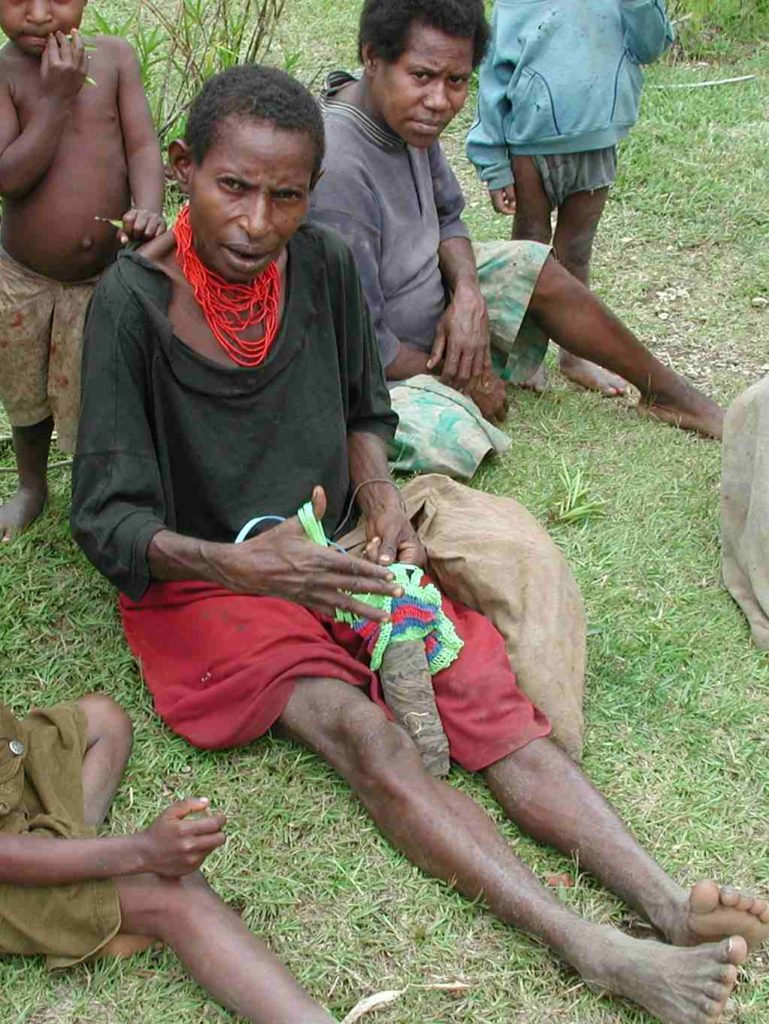 A Malaumanda woman in typical, daily dress weaving a string bag.